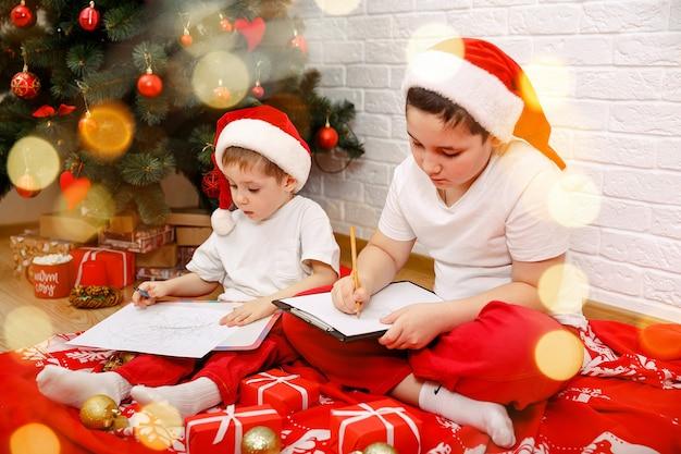 Meninos compartilhando seus sonhos na véspera de natal perto da árvore de natal