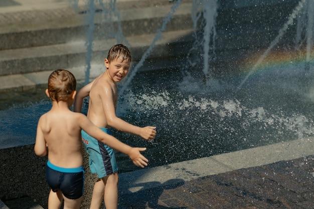 Meninos correndo e brincando na fonte da cidade em um dia quente de verão em são petersburgo, rússia