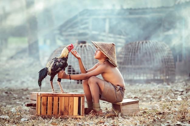 Meninos, crianças de fazendeiros tailandeses brincando com gamecocks qual é seu animal de estimação foi lembrado depois de voltar de uma escola rural