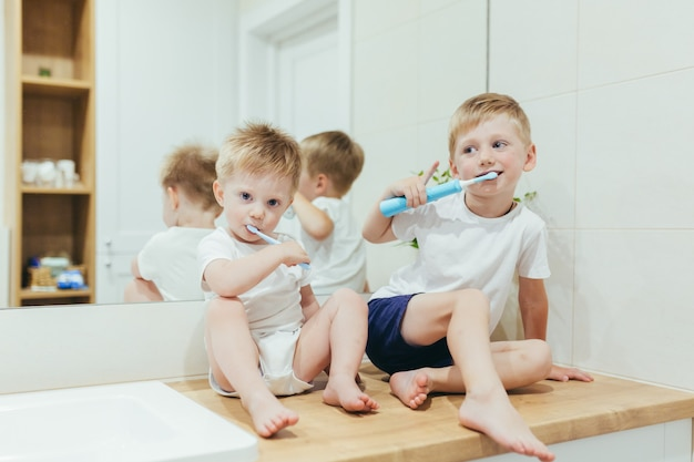 Meninos, crianças escovando os dentes no banheiro, dois irmãos
