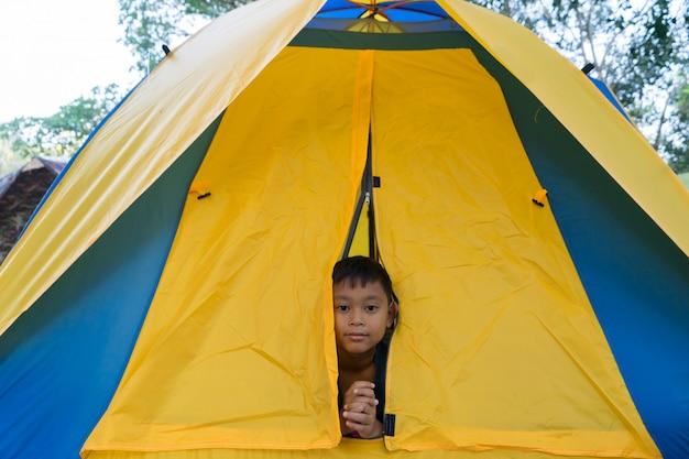 Meninos da criança estão na tenda durante o acampamento.