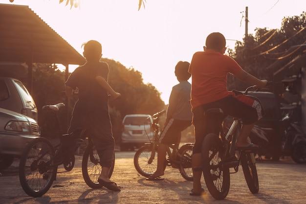 Meninos de bicicleta na rua residencial observando o pôr do sol