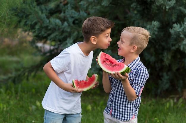 Meninos de crianças felizes comendo melancia no verão