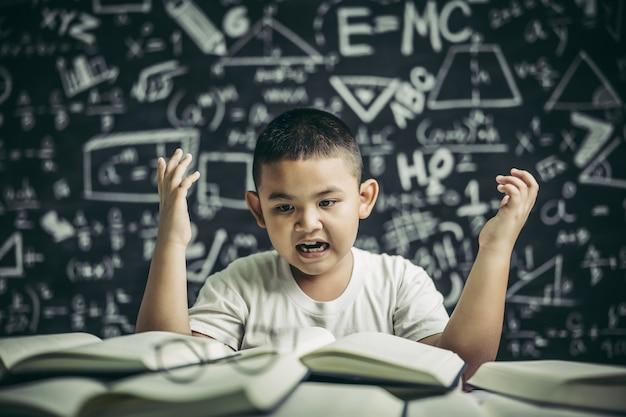 Meninos de óculos escrevem livros e pensam na sala de aula
