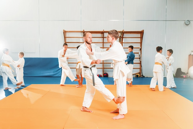 Meninos de quimono praticam arte marcial no ginásio de esportes. kid judô, jovens lutadores em treinamento no corredor.