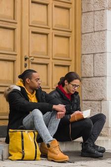 Meninos de tiro completo, sentado na escada com notebook