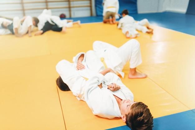 Meninos de uniforme, treinamento infantil de judô