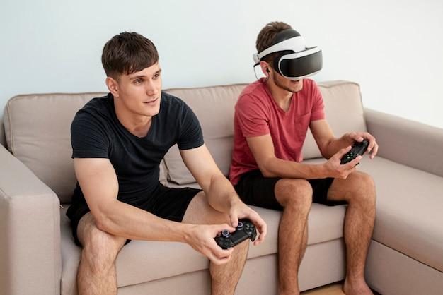 Meninos de vista lateral brincando com controladores e óculos vr