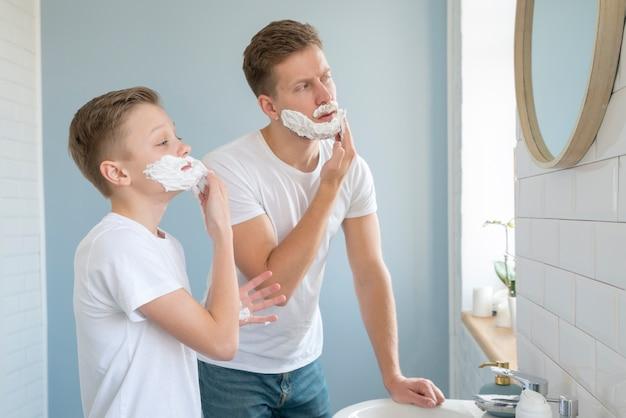 Meninos de vista lateral usando espuma de barbear