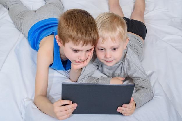 Meninos deitado na cama e olhando para o tablet