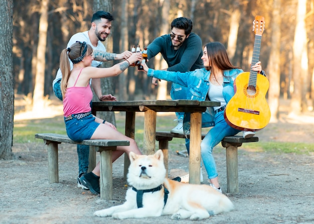 Meninos e meninas com seu cachorro comemorando a festa de fim de semana em uma área de piquenique Foto Premium