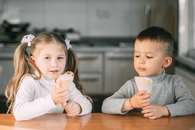 Meninos e meninas comendo sorvete de casquinha na cozinha é muito divertido, muito doce