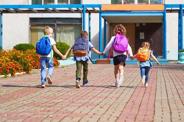 Meninos e meninas correndo para a escola primária.