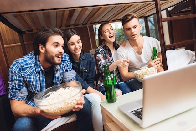 Meninos e meninas estão assistindo filme no laptop com pipoca.