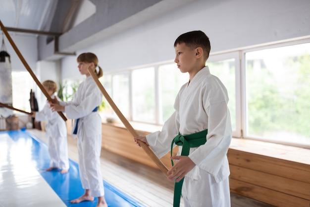 Meninos e meninas se sentindo seriamente aprendendo aikido no fim de semana