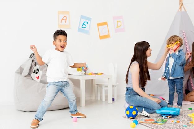 Meninos e mulher tocando juntos em casa