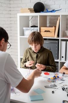 Meninos e professor se divertindo construindo carros-robôs juntos na oficina