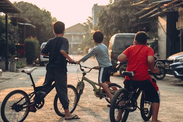 Meninos em idade escolar andam de bicicleta ao ar livre em uma área residencial