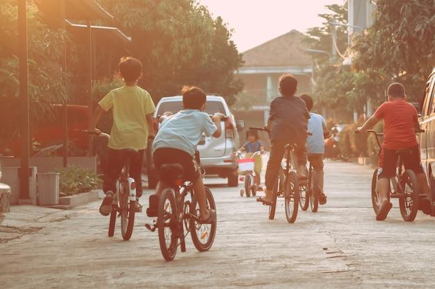 Meninos em idade escolar pedalando em uma rua residencial