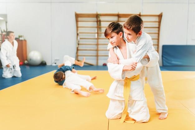 Meninos em lutas de quimonos, treinamento infantil de judô