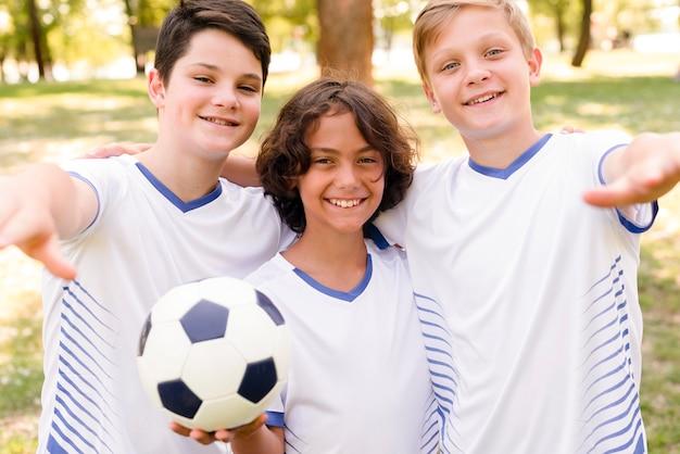 Meninos em roupas esportivas posando ao ar livre