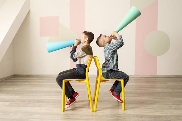 Meninos engraçados com megafones de papel dentro de casa