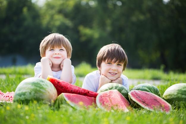 Meninos engraçados comendo melancia ao ar livre no parque de verão.