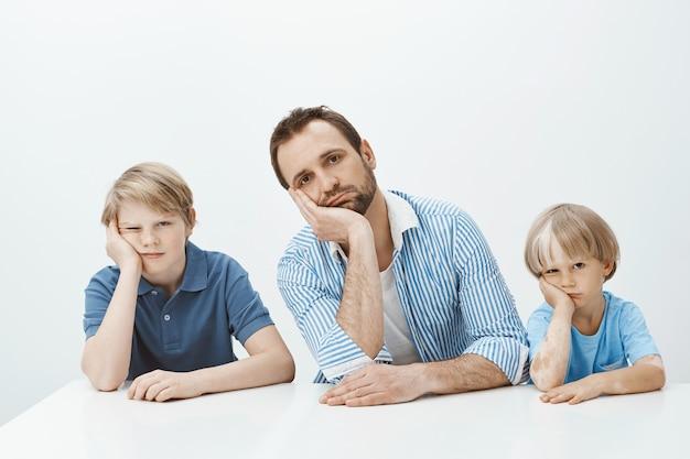 Meninos entediados e chateados. retrato de uma família europeia engraçada cansada de filhos e pai sentado à mesa, apoiando a cabeça nas palmas das mãos e olhando indiferente