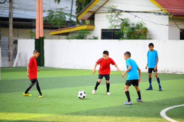 Meninos jogando futebol no campo de treino de futebol