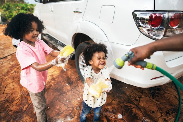 Meninos lavando o carro da família