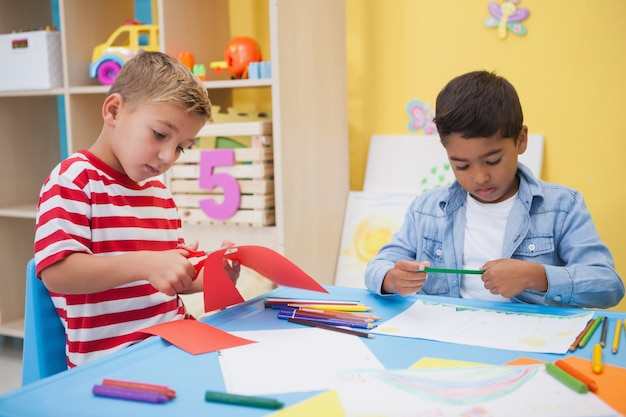 Meninos pequenos bonitos desenhando na mesa