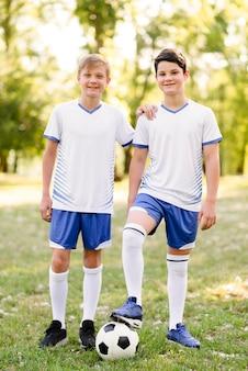 Meninos posando com uma bola de futebol ao ar livre