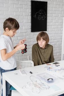 Meninos se divertindo construindo carros-robôs juntos na oficina