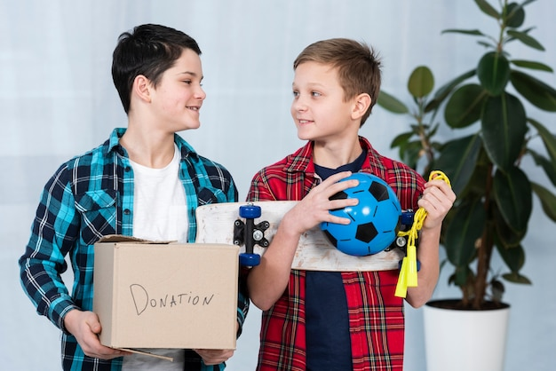 Meninos segurando caixa de doação
