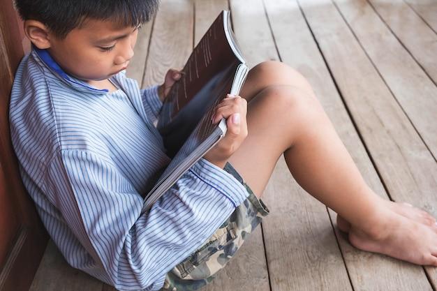 Meninos sentados lendo um livro sozinho