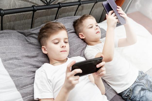 Meninos tristes irmãos estão deitados na cama com telefones nas mãos.