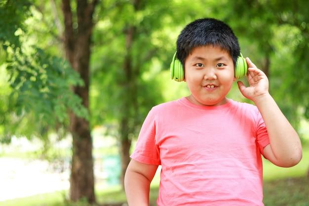 Meninos usando fones de ouvido verdes sorriso feliz no jardim natural