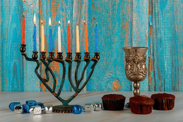 Menora com nove velas acesas, pião e cupcakes
