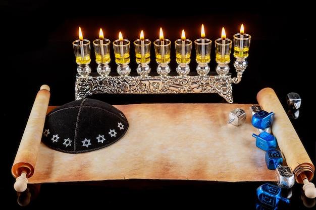 Menorá com velas de óleo acesas e quipá com maquete da torá para hanukkah. feriado judaico.
