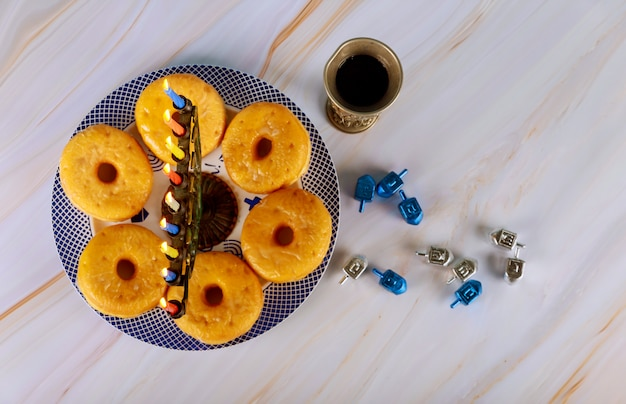 Menorá de hanukkah e rosquinhas no prato com vinho e pião