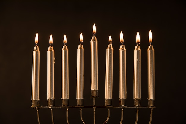 Menorá dourada com velas flamejantes