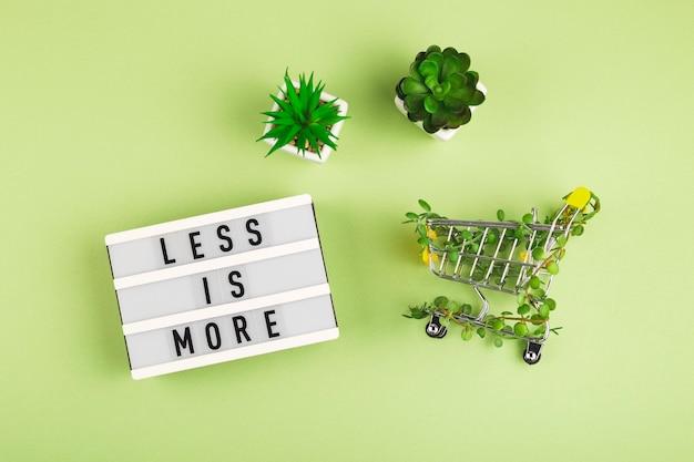 Menos é mais escrito na mesa de luz ao lado do carrinho de compras entrelaçado com plantas e suculentas em vasos ...