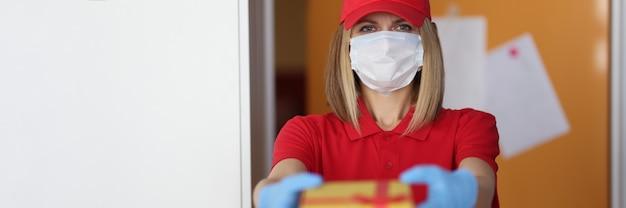 Mensageira com máscara médica protetora e luvas dando um presente