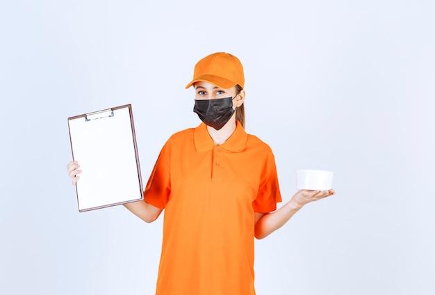 Mensageira com uniforme laranja e máscara preta segurando um copo de plástico e uma lista de clientes