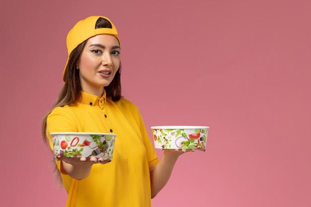 Mensageira de frente com uniforme amarelo e capa segurando tigelas redondas na parede rosa serviço uniforme trabalho de entrega