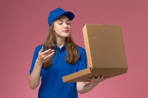 Mensageira de frente com uniforme azul segurando uma caixa de entrega de comida cheirando na mesa rosa.