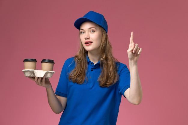 Mensageira de frente com uniforme azul segurando xícaras de café marrons na mesa rosa. empresa de entrega de uniforme