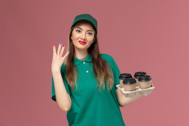 Mensageira de frente com uniforme verde e capa segurando xícaras de café de entrega sorrindo ligeiramente na parede rosa serviço de entrega uniforme.