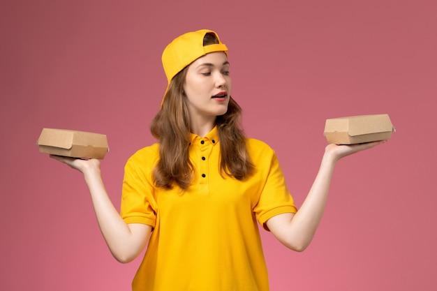 Mensageira de frente feminina em uniforme amarelo e capa segurando pequenos pacotes de comida de entrega na parede rosa serviço trabalhador entrega uniforme