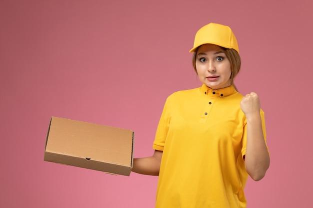 Mensageira de frente para mulher com capa amarela uniforme segurando caixa de comida na mesa rosa.